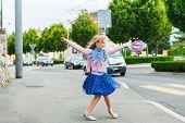 Adorable little girl dancing in the street, walking home after dance school