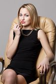 stock photo of bitchy  - Attractive young woman wearing evening dress sitting in armchair while making up - JPG