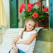 Adorable little girl resting on a bench on a nice warm summer day, outdoors