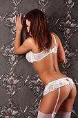 image of seduction  - Sexy brunette woman at night posing on vintage wall seduction - JPG
