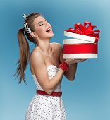 Surprised laughing beautiful young woman holding an open gift box over blue background. Holidays, ho