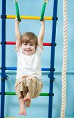 stock photo of gymnastic  - cute child boy hanging on gymnastic rings at home - JPG