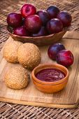 picture of satsuma  - Small wooden bowl of plum jam with wholegrain buns and satsuma plums on wooden board photographed with natural light  - JPG