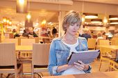 Woman sitting in the cafe using digital tablet