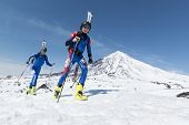 Ski Mountaineering: Two Ski Mountaineer Climb To Mountain With Skis Strapped To Backpack