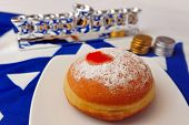 stock photo of hanukkah  - Photo of a white and blue Israeli flag with the star of david with chocolate coins sufganiya and silver menora  - JPG