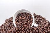 ceramic white mug on a pile of roasted coffee beans