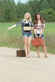 Students girls hitchhike with cardboard