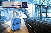 Departure For Rosenburg, Germany. Blue Suitcase At The Railway Station