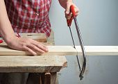 stock photo of sawing  - Sawing wooden pine board with the hand saw indoor composition - JPG