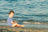 Playful Toddler With Sailor Shirt Sitting At The Edge Of The Waves On A Beach. Photo With Untraditio