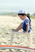 Sweet Toddler Dressed As A Sailor Sitting On A Plastic Table On A Beach. Photo With Untraditional Co