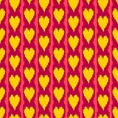 Colorful heart shape ikat seamless pattern in yellow and red, vector