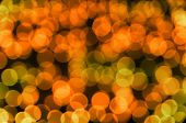 Festive colored glowing abstract circular bokeh orange green background