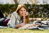 stock photo of exams  - young beautiful student girl lying on campus park grass with books on rug studying happy preparing exam in university and college education concept - JPG