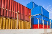 Colorful Industrial Cargo Containers Behind Metal Fence