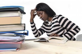 image of piles  - young stressed black African American ethnicity student girl studying pile of books on library desk preparing exam in stress feeling tired and overwhelmed in youth education concept - JPG