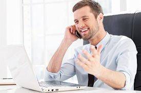 stock photo of adults only  - Happy young man in formalwear looking at computer monitor and talking on the mobile phone while sitting at his working place - JPG