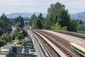 image of passenger train  - A passenger train moving towards trees and a cityscape - JPG