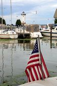 picture of lighthouse  - This image features an American flag in the foreground with boats and the Fond du Lac Lighthouse in the background - JPG