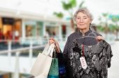 picture of mall  - Graceful old woman shopping in the mall with three shopping bags in left hand - JPG