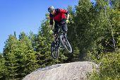 foto of dirt-bike  - Mountain bike rider jumps over a dirt track kicker - JPG