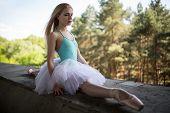 pic of tutu  - Graceful ballerina in white tutu sitting in the splits on a concrete bridge support - JPG