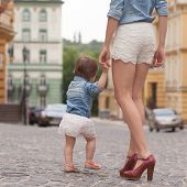 picture of stroll  - Young mother strolling with tiny daughter on street - JPG