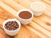 foto of coffee grounds  - Three cups with coffee coffee beans and ground coffee on wooden table - JPG