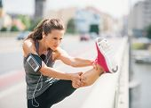 picture of stretch  - An athletic woman stretches out before going on a long run - JPG