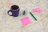 stock photo of ballpoint  - Blue coffee mug and paper with ballpoint on map - JPG