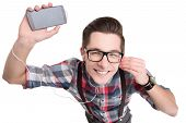 stock photo of nerds  - Young nerd in glasses and checkered shirt listening to music with smartphone isolated on white background - JPG