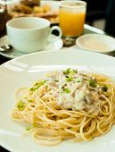 stock photo of carbonara  - pasta carbonara with juice and tea on table - JPG