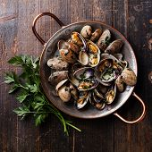stock photo of clam  - Shells vongole venus clams with parsley in copper cooking dish on dark wooden background - JPG