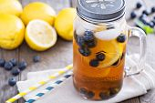 foto of masonic  - Ice tea in mason jar mug with lemon and blueberries refreshing in hot summer day - JPG