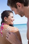 stock photo of sun-tanned  - Handsome man putting sun tan lotion on his girlfriend at the beach - JPG