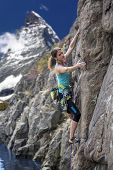 picture of mountain-climber  - Elegant female alpine climber ascents natural rock Alps mountain landscape - JPG