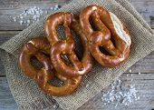stock photo of pretzels  - Fresh pretzels with sea salt on wooden table - JPG