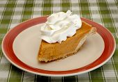 pic of pumpkin pie  - Fresh pumpkin pie sliced to serve with topping - JPG