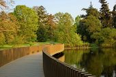 image of pedestrians  - Pedestrian bridge through the lake in spring park - JPG