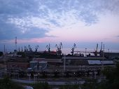 image of distort  - View of a cargo seaport against the evening cloudy sky with wide angle distortion view - JPG