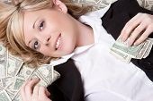 pic of greedy  - Smiling woman laying in money - JPG