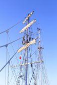 stock photo of mast  - Tall sailing ship mast against a clear blue sky - JPG