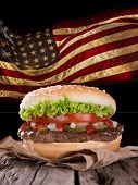 picture of hamburger-steak  - Delicious hamburger with fire flames and american flag on wooden background - JPG