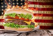 pic of hamburger-steak  - Delicious hamburger with fire flames and american flag on wooden background - JPG