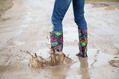 picture of woman boots  - Woman with rain boots jumps into a puddle - JPG