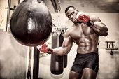 stock photo of boxing  - African black male boxer punching ball wearing boxing gloves in gym - JPG
