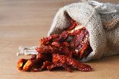 foto of sleeping bag  - Dried tomatoes got enough sleep from canvas bag at wooden background - JPG