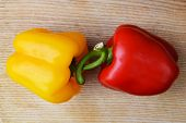 foto of yellow-pepper  - red and yellow ripe peppers lies on wooden cutting board - JPG