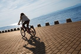 stock photo of superimpose  - Girl rides a bike on the promenade by the sea at sunset - JPG